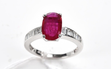 A RUBY AND DIAMOND RING IN 18CT WHITE GOLD, THE OVAL CUT RUBY WEIGHING 1.69CTS, SHOULDERED BY BAGUETTE CUT DIAMONDS TOTALLING 0.58CT...