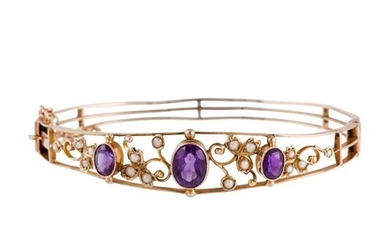A VICTORIAN AMETHYST AND SEED PEARL BANGLE, mounted in yello...