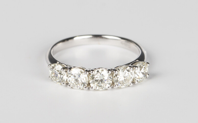 A white gold and diamond five stone ring, claw set with a row of circular cut diamonds, detailed
