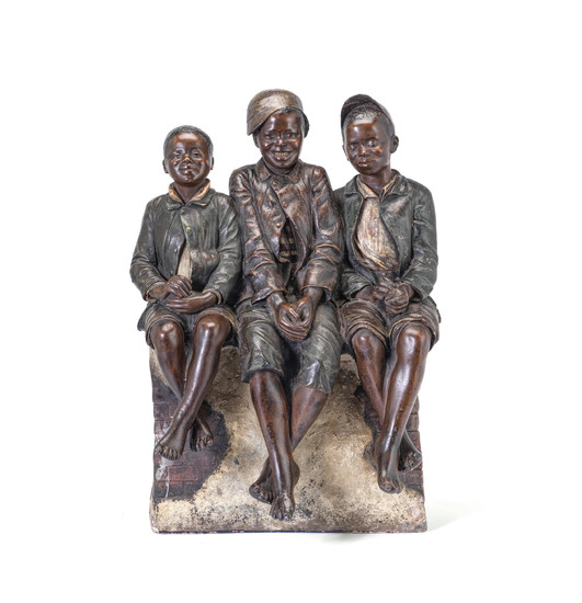 An early 20th century Austrian painted terracotta novelty figural group of three seated boys