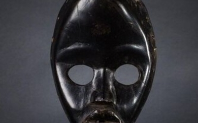 FACIAL MASK. Hard wood with black lacquered patina, round open eyes, prominent mouth with thick lips. Ivory Coast Dan. Height 22.5 cm
