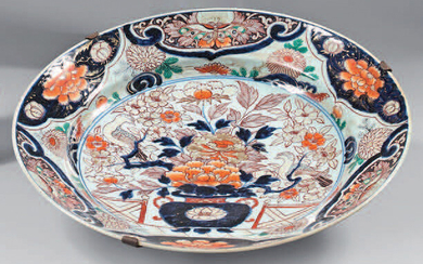 Large Japanese porcelain dish (Arita). 17th century, circa 1680. Imari decoration, in the center of a vase of flowers in front of a hedge with birds in a medallion, the wing and the fall of a frieze of mantling with flowers and butterflies, the...