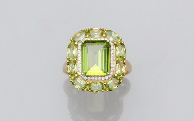 Yellow gold ring, 750 MM, set with an emerald-cut peridot with cut sides weighing about 6 carats in a row of diamonds surrounded by a frieze of peridots, size: 54, weight: 6.1gr. rough.