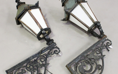 A pair of 20th century Continental cast iron wall mounted street lanterns with foliate scrolling sup