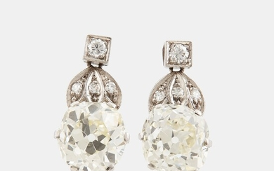 A pair of platinum earrings set with cushion formed old-cut diamonds with a total weight of ca 6.00 cts quality ca L/M v