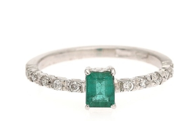 An emerald and diamond ring set with an emerald weighing app. 0.41 ct. flanked by ten diamonds, mounted in 18k white gold. Size 52.5.