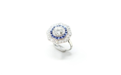 Art Deco ring with an octagonal platinum bezel centered on an antique cut diamond in a double surround of calibrated sapphires and 8/8 cut diamonds.