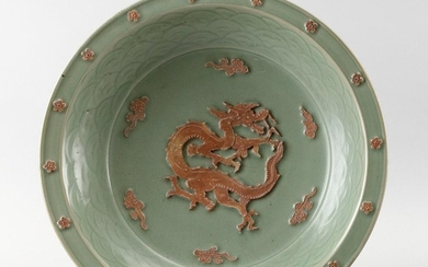 CHINESE LONGQUAN CELADON PORCELAIN SHALLOW BOWL Raised unglazed decoration of a dragon amidst fiery pearls surrounded by a wave inne...