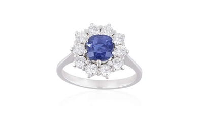 Description A SAPPHIRE AND DIAMOND CLUSTER RING The cushion-shaped...