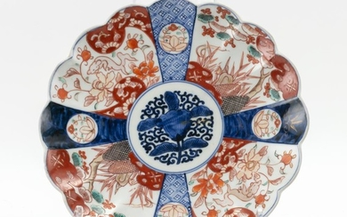 """JAPANESE IMARI DISH In sixteen-petal flower form, with a lotus center and a shishi crane and flower border. Diameter 10.3""""."""