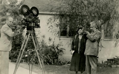Photograph of Einstein holding a home movie camera, pointing it at the pioneering documentary filmmaker Merl LaVoy.