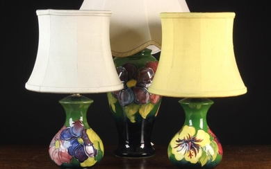Three 20th Century Moorcroft Lamps: The largest of baluster form decorated with clematis on a dark b