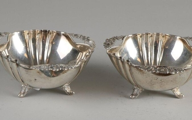 Two silver dishes, 925/000, triangular contoured with ribs, with 3 handles made of flowers. The dishes are placed on 3 worked curled legs. 11x11x4.5cm. total approx. 129 grams. Both slightly dented. Otherwise in good condition