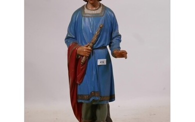 A carved and painted wood figure of a young man in medieval ...