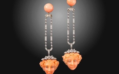 A pair of coral and diamond drop earrings, the coral cabochons suspend articulated diamond-set drops, and carved coral faces with diamond-set eyes in platinum, 8.5cm high, fitted case