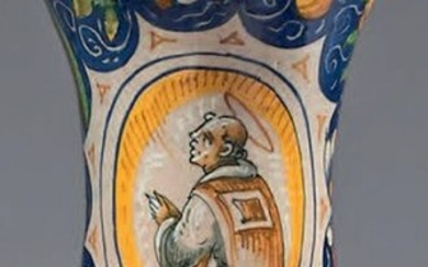 Albarello in Italian majolica (Venice, probably the workshop of Maestro Domenico) from the mid-16th century. Of curved shape, with blue, green, ochre decoration of a representation of a monk in two thirds in a radiating oval cartouche framed with large...