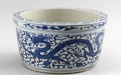 CHINESE BLUE AND WHITE PORCELAIN JARDINIÈRE Decoration of a phoenix and dragon chasing a fiery pearl on a lotus and vine field. Six-...