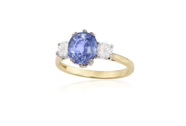 Description A SAPPHIRE AND DIAMOND RING The oval-shaped sapphire...