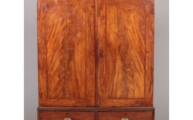 A George III figured mahogany cottage linen press raised on ...