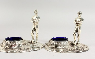 A PAIR OF TABLE SALTS, modelled as early footballing