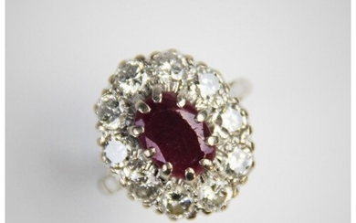 A ruby and diamond cluster ring, comprising a central oval m...