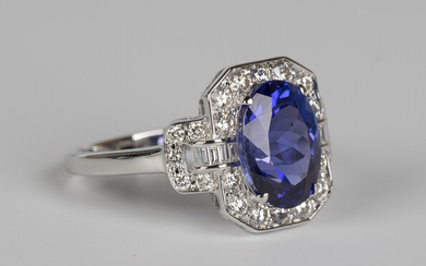 An 18ct white gold, tanzanite and diamond ring, claw set with an oval cut tanzanite within a canted