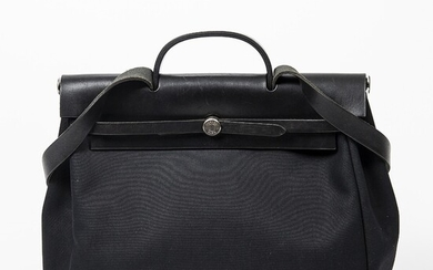 """Hermès: A """"Herbag"""" made of black canvas and leather with silver toned hardware, a short..."""