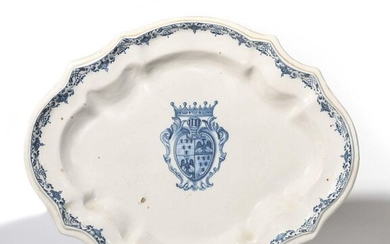 Midi Oval dish with contoured rim in earthenware with blue monochrome decoration in the center of a coat of arms in a shield under a crown and foliated scrolls on the rim. 18th century. L. 42 cm