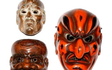 THREE JAPANESE LACQUERED MASKS MEIJI PERIOD, 19TH AND 20TH CENTURY The largest in red and black lacquer, carved as a grimacing face with a long beak-like nose, possibly depicting a tengu; another with the eyebrows, moustache and goatee made of hair...