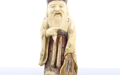 A Japanese carved and painted ivory okimono depicting a Sage...