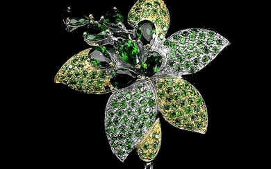 A brooch set with numerous circular-cut peridots and chrome diopsides, mounted in rhodium plated sterling silver. 5.5×3.9 cm.