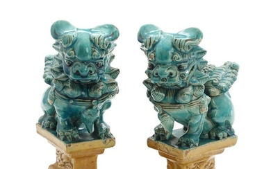 A pair of 20th century Chinese ming style earthenware guardian lions on bases. H. 24...