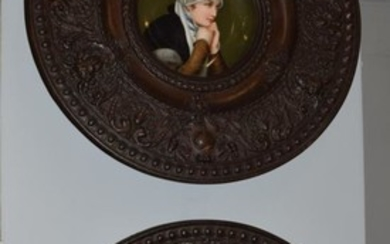 A pair of circular brass plaques with central porcelain plaques...