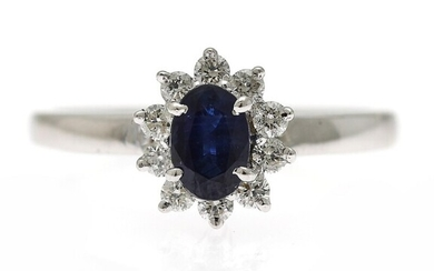A sapphire and diamond ring set with an oval-cut sapphire encircled by numeros diamonds, mounted...