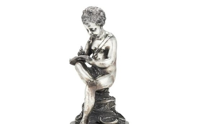 An Italian filled silver coloured figure of a seated putto writing