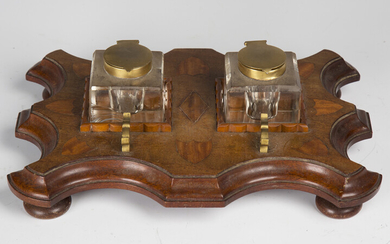 An early 20th century mahogany and satinwood inkstand, fitted with two glass inkwells on a serpentin