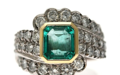 An emerald and diamond ring set with an emerald weighing app. 3.00 ct. encircled by...
