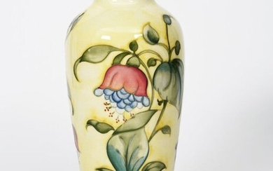 Fuchsia' a Moorcroft Pottery vase designed by Walter Moorcroft, shouldered form with collar rim, tubeline decorated with flower stems in purple, blue and green on a yellow ground impressed factory marks, painted blue signature, 31cm. high
