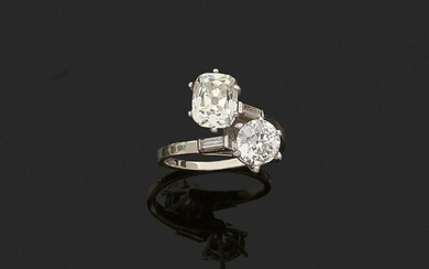 "RING ""Toi & Moi"" in 750 thousandths white gold and 850 thousandths platinum, set with an antique cut round diamond and an antique cut cushion diamond between two rectangular diamonds. Finger size : 53. Gross weight: 4.4 g. Assumed diamond weight: the..."