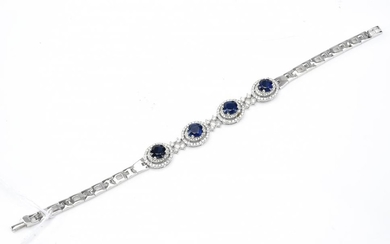A KYANITE AND DIAMOND BRACELET-Featuring four cushion cut kyanites, each within a double border of round brilliant cut diamonds, wit...