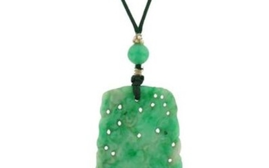 A carved jadeite jade pendant, suspended from a...