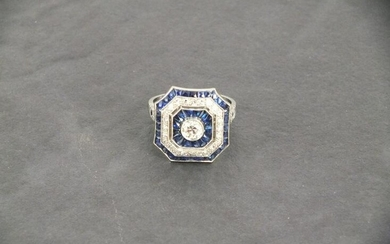 A platinum square shaped ring with chamfered corners, set...