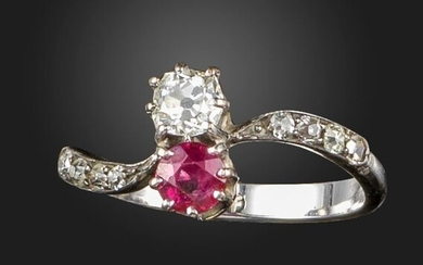 A ruby and diamond crossover ring, set with a circular-cut ruby and an old cushion-shaped diamond, with further old circular-cut diamonds to the shoulders in white gold, size P