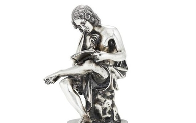 An Italian filled silver coloured figure of a seated youth reading