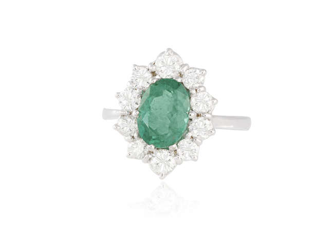 Description AN EMERALD AND DIAMOND CLUSTER RING The oval-shaped...