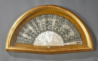 Folded type fan, the strands and frame in mother-of-pearl, silk leaf and black embroidery with openwork decoration of stylized foliage and volutes. The end of a plume decorated with a number.