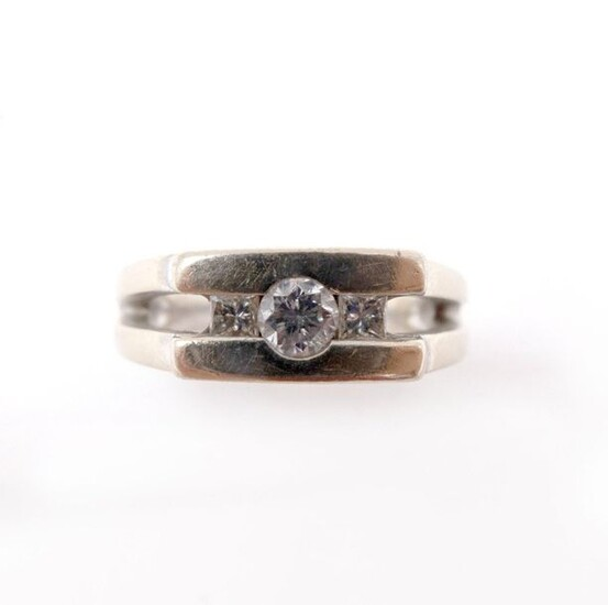 RING in 18K white gold holding one brilliant-cut diamond surrounded by two princess cut diamonds. French work. TDD: 52. Raw weight : 11.42 gr. A gold and diamond ring.
