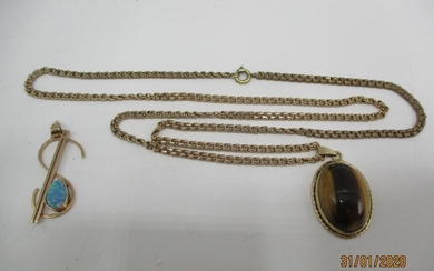 A 9ct gold pendant set with tigers eye on a yellow metal cha...