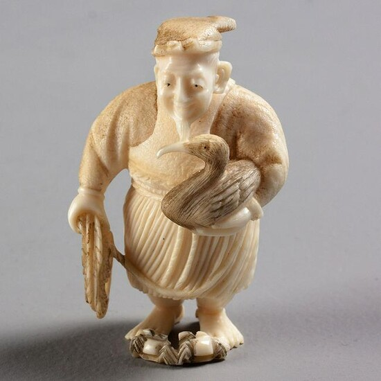 A JAPANESE IVORY NETSUKE OF A CORMORANT FISHERMAN