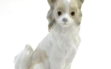 A Nao figurine modelled as a seated long haired